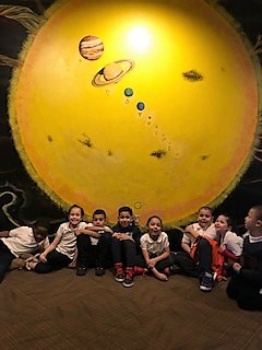 group picture of students in front of a picture of a planet at their field trip