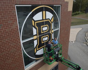 workers install sun shade in form of Bruins logo