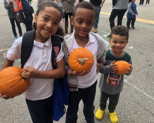three kids holding pumpkin
